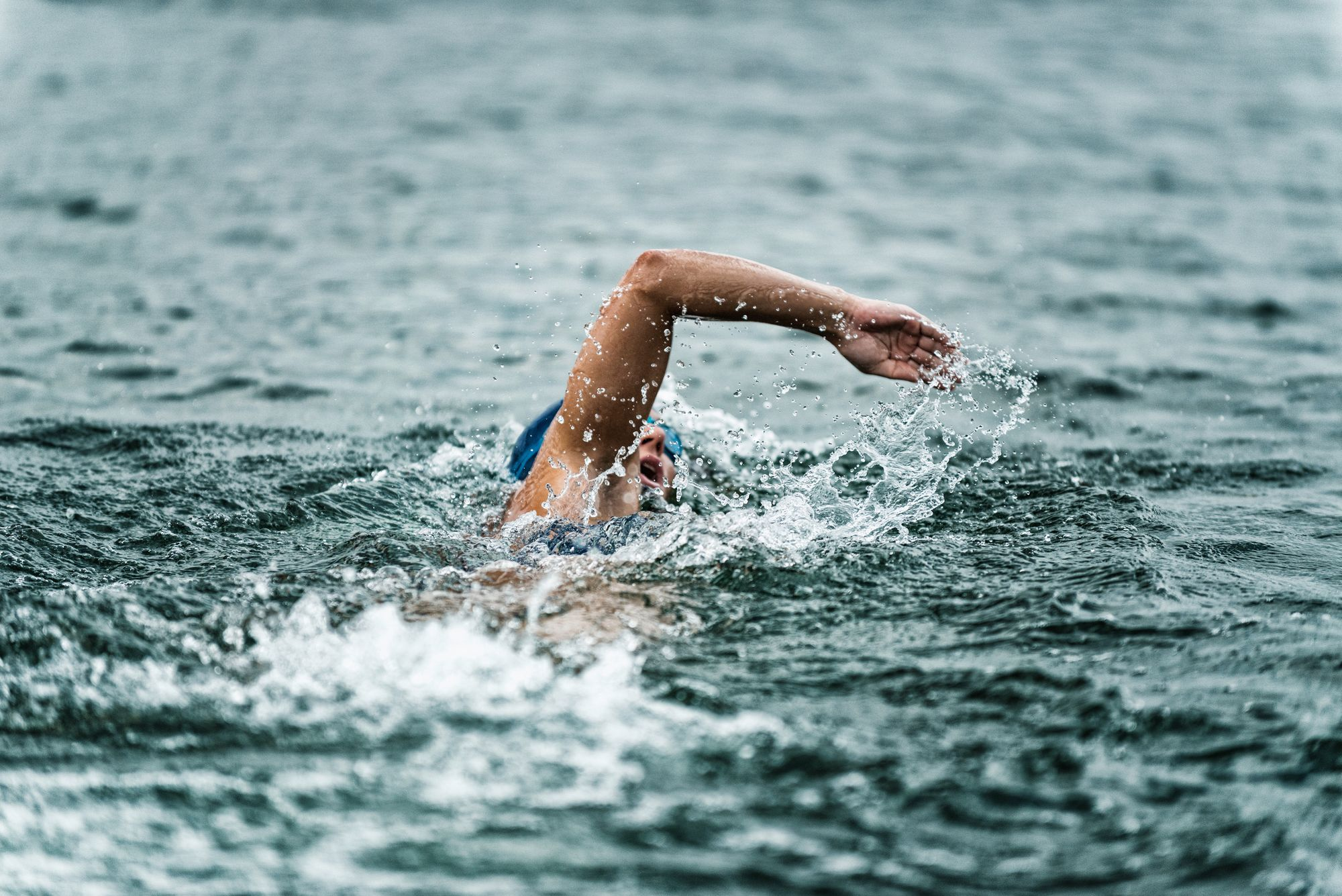Open water swimmer doing strokes in the sea